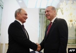 Russia's President Vladimir Putin (left) shakes hands with his Turkish counterpart, Recep Tayyip Erdogan, during their meeting in Tehran on September 7. Putin voiced opposition to Erdogan's call for a cease-fire.