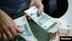 Russia -- An employee of a bank counts ruble banknotes in Moscow, September 2, 2014