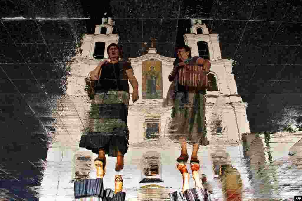 Two women walk in front of the Holy Spirit Orthodox cathedral as they are reflected in the wet tablets of a roadway in the Belarusian capital, Minsk. (AFP/Sergei Gapon)