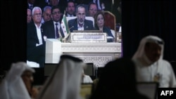 Moaz al-Khatib, head of the Syrian opposition delegation, appears on-screen as he addresses the opening of the Arab League summit in Doha on March 26.