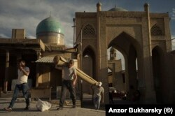 """Men carry a carpet into a marketplace in the center of Bukhara that was demolished by the authorities soon after this 2017 photo was taken. The market demolition was part of the controversial """"accelerated development"""" of many historic sites in Uzbekistan."""