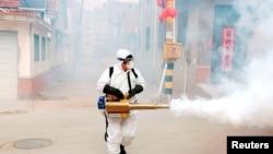 Работник дезинфекцира улиците на китайски град в провинция Шандун