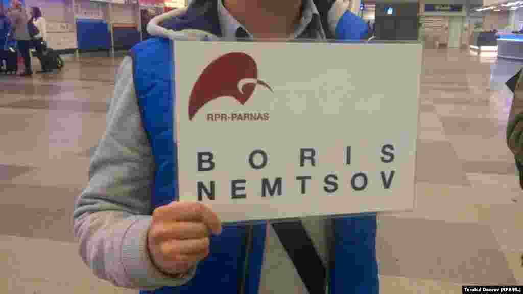 """Гражданский активист держит табличку """"Борис Немцов"""" в зале ожидания пассажиров рейсов, прилетающих из России. Прага, 2 апреля 2015 года."""