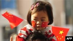 Ұлттық мейрам күні қызын көтеріп келе жатқан қытай азаматы. Бейжің, 1 қазан 2009 жыл.