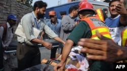 Pakistani volunteers remove a body from the Federal Investigation Agency building after gunmen attacked it in Lahore.