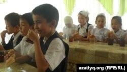 Ученики младших классов средней школы за завтраком в школьной столовой. Иллюстративное фото.