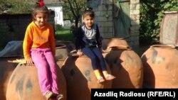 Uşaqlar hazır təndirin üstündə oturublar. Astaranın Züngüləş kəndi, sentyabr 2019