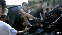 Сирийские ополченцы помогают раненому во время столкновений на западе Сирии, 21 июня 2012 г.