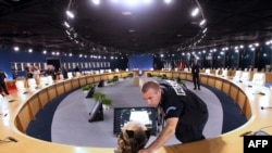 Специалисты проверяют условия безопасности в зале заседаний участников саммита в Каннах