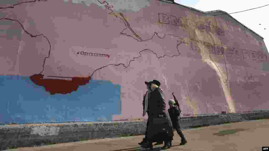 "Women and a boy with a toy assault rifle walk past an unfinished wall painting in Moscow depicting a map of the Crimean peninsula and a slogan reading, ""Together Forever."" (AFP/Alexander Nemenov)"