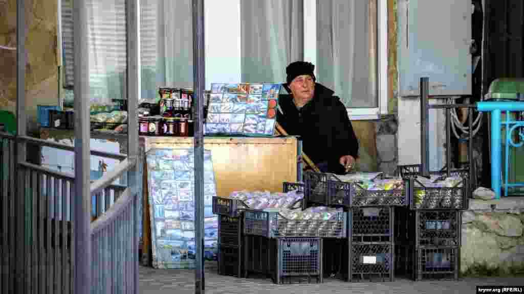Скучающий продавец сувениров. Ассортимент в торговых рядах варьируется от магнитиков и посуды с пейзажами Крыма до теплых вещей и варенья из ягод и фруктов