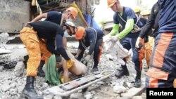 Филиппинские спасатели работают на месте разрушения зданий. Себу, 15 октября 2013 года.