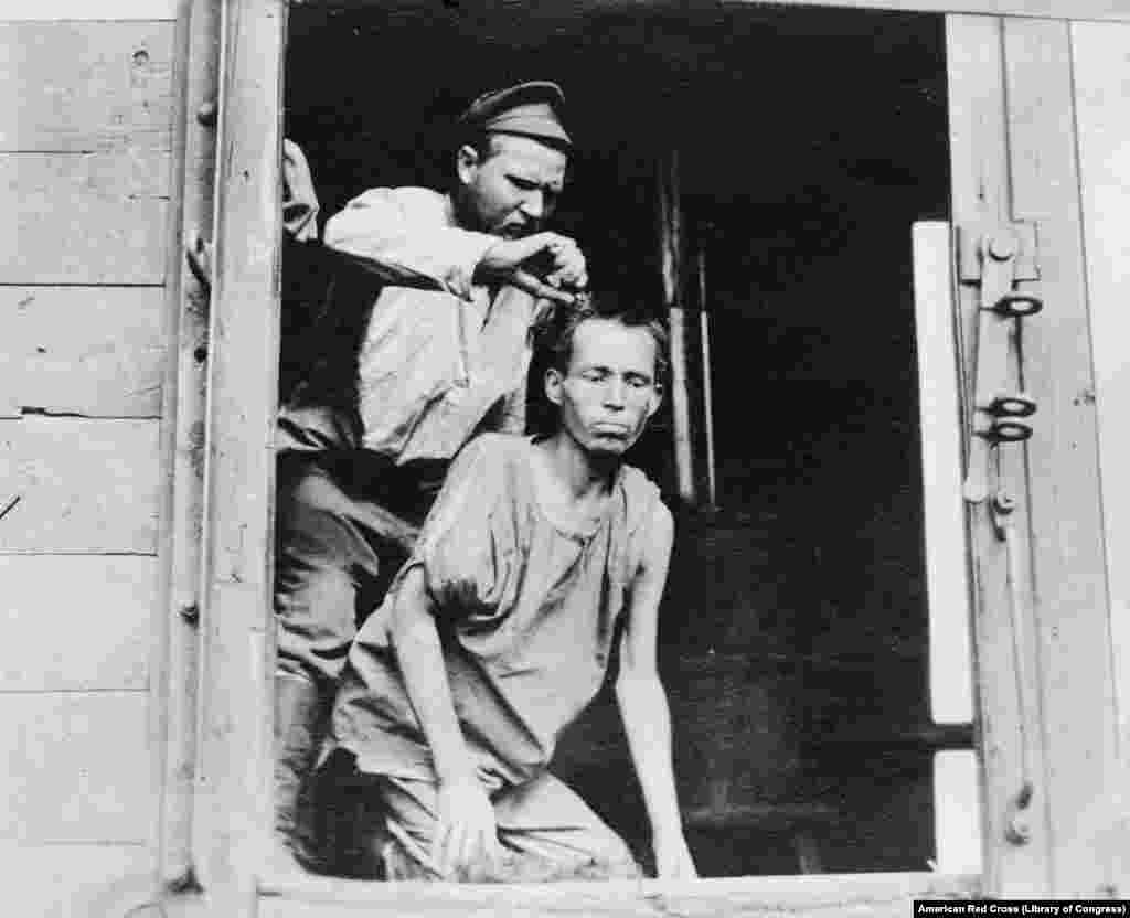 """რუს ჯარისკაცს თმას კრეჭენ. წითელი ჯვრის ერთ-ერთი თანამშრომლის სიტყვებით, ტყვეობიდან გათავისუფლებული ჯარისკაცები """"გერმანიაზე გაბოროტებული, რუსეთის მოქმედი მთავრობის მიმართ ზიზღით სავსე და ამერიკელების მადლიერი"""" იყვნენ."""