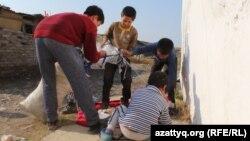 Дети Дильбар Куттыбай собирают полиэтиленовые пакеты на улице. Шымкент, 31 октября 2016 года.