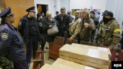 Ukrainian activists block the printing of election ballots at a printing press in Mariupol on October 19. Some fear Ukraine's richest oligarch will manipulate the vote.