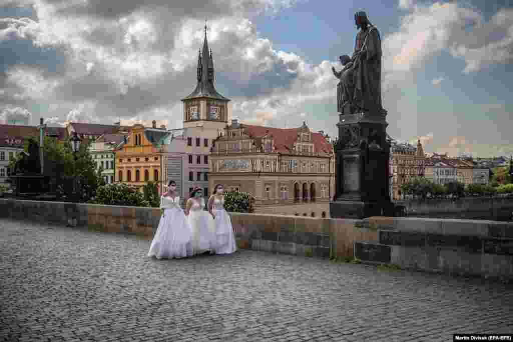 Models wearing protective face masks and wedding dresses walk on the Charles Bridge as they take part in a commercial shoot in Prague. (epa-EFE/Martin Divisek)