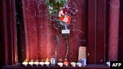 Цветы и свечи у разбитой выстрелами витрины парижского ресторана Карийон, во время стрельбы в котором погибли более 10 человек