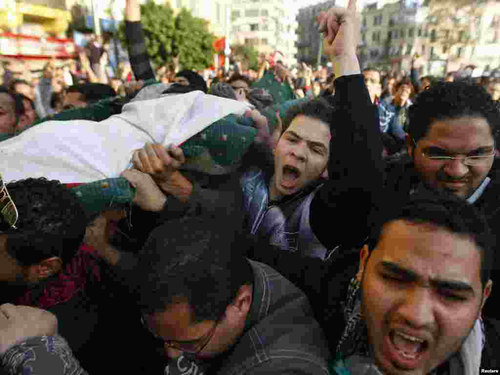 Demonstrators carry the body of a man killed during an attempt to storm the interior Ministry in Cairo.
