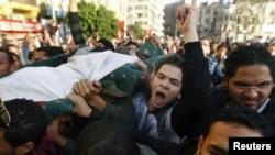 Протестующие несут тело убитого при попытке штурма здания министерства внутренних дел. 29 января 2011г.