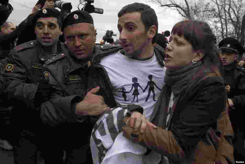 Police detain an Orthodox Christian activist after a scuffle with gay-rights activists.