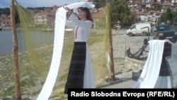 Дрвена кукла која бели платно е поставена на градското пристаниште во Охрид.