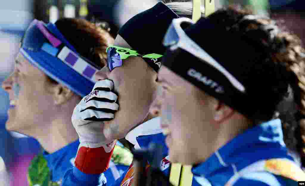 Finland's Anne Kylloenen (center) Aino-Kaisa Saarinen (left) and Kerttu Niskanen of Finland react at the finish line during the women's cross-country 4 x 5km relay competition. Finland won silver. (EPA/Filip Singer)
