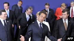 French President Nicolas Sarkozy gestures as he and other EU leaders leave a family photo at the start of the European Council summit in Brussels on June 17.