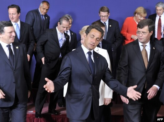 French President Nicolas Sarkozy gestures as he and other EU leaders leave a family photo at the start of the European Council summit in Brussels on June 17 2010 (Photo: AFP)