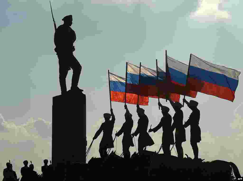 Horseriders hold the Russian national flag next to a bronze statue of a Russian soldier in Moscow during celebrations of the National Flag Day on August 22. (AFP/Vasily Maximov)