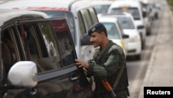A police trooper checks a car at a checkpoint on the road leading to Sanaa International Airport on August 6.