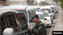 Сотрудник йеменских сил безопасности осматривает автомобиль. Иллюстративное фото.