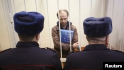 Russian photographer Denis Sinyakov stands in the dock during a court session in St. Petersburg on November 18, at which his bail was set at around $61,000.