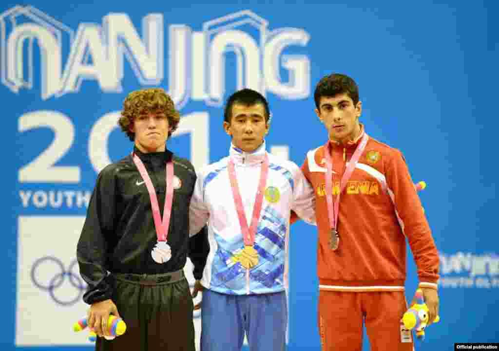 Нанкиндегі жасөспірімдер олимпиадасының алтын медалін жеңіп алған жас балуан Мұхамбет Қуатбек (ортада) марапаттау рәсімі кезінде. Нанкин, 27 тамыз 2014 жыл.
