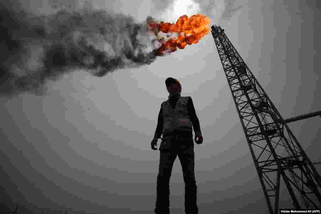 An employee stands amid the Zubair oil and gas field, north of the southern Iraqi province of Basra. (AFP/Haidar Mohammed Ali)