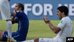 Форвард Уругвая Луис Суарес (справа) и итальянский защитник Джорджо Кьеллини во время матча Уругвай - Италия на ЧМ по футболу в Бразилии, 24 июня 2014 года.