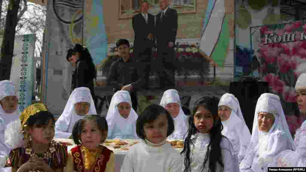 Балалар мен қарт әйелдер Қазақстан президенті Нұрсұлтан Назарбаев пен Өзбекстан президенті Ислам Каримов портретінің тұсында отыр. Мерекелік шараны Қазақ мәдениеті орталығы ұйымдастырған. Ташкент, 21 наурыз 2015 жыл.
