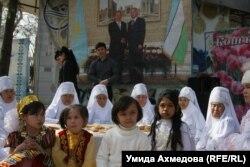 Дети и пожилые женщины сидят на фоне большого фотопортрета президентов Казахстана Нурсултана Назарбаева и Узбекистана Ислама Каримова на праздновании Наурыза, организованном Казахским культурным центром. Ташкент, 21 марта 2015 года.