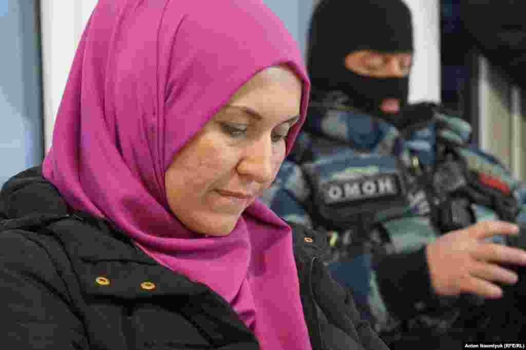 Правозащитница Лиля Гемеджи на фоне бойца ОМОНа на заседании «Крымской солидарности»