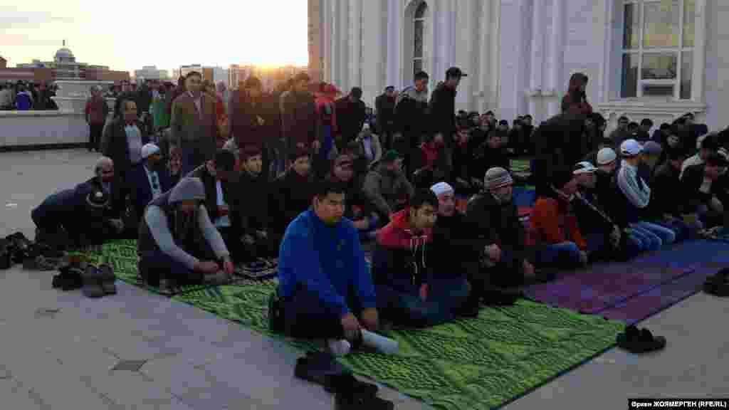 Верующие сидят снаружи мечети «Хазрет Султан» в ожидании айт-намаза.
