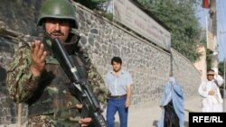 An Afghan police commando surveyed the scene after two Taliban militants were killed in a gun battle near the Afghan national peace jirga in Kabul.