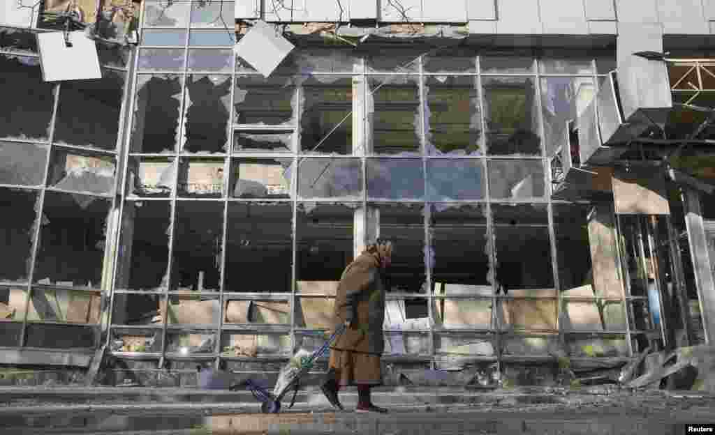 A woman pulls her shopping trolley as she walks past a building that was damaged by shelling in Donetsk, eastern Ukraine, on October 15. (Reuters/Shamil Zhumatov)