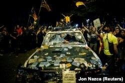 Сторонники независимости Каталонии и поврежденная ими автомашина Гражданской гвардии Испании. Таррагона, 22 сентября