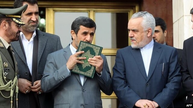 Mahmud Ahmadinejad kisses a copy of The Koran before leaving for a foreign visit in March 2013.