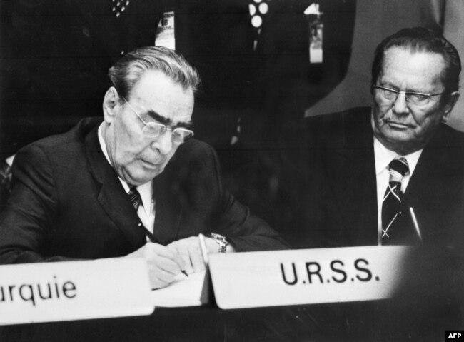 Леонид Брежнев подписывает Хельсинкский акт. Справа - лидер социалистической Югославии Иосип Броз Тито