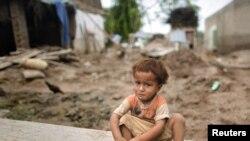 Ребенок у дома, разрушенного наводнением в Пакистане.