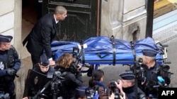 A man moves the body of one the three Kurdish women who were found killed with a gunshot to the head at the Kurdish Institute in Paris.