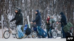 Беженцы пересекают пограничный пост Норвегии на границе с Россией. Стурскуг, 12 ноября 2015 года.