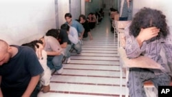 While covering their faces, Iranian youth who had been arrested in student protests, sit in a hallway of the Evin prison, in Tehran, Iran, Sunday, June 15, 2003.