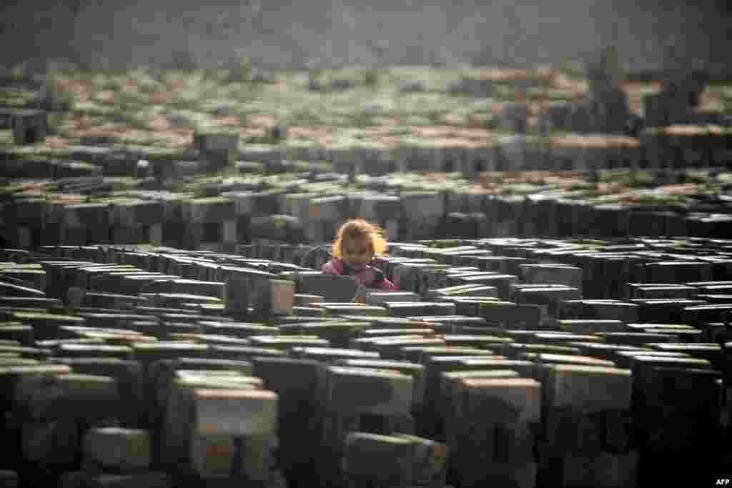 An Iraqi girl stands amid bricks being baked dry in the sun at a factory near the shrine city of Najaf. (AFP/Haidar Hamdani)