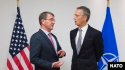 NATO Secretary-General Jens Stoltenberg (right) speaks with U.S. Defense Secretary Ash Carter at the start of a NATO defense ministers meeting in Brussels on October 8.